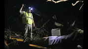 A responder shines his flashlight into the remains of several mobile homes as he searches for survivors in Louisville, Miss., on April 29, 2014, after a tornado hit the east Mississippi community Monday.