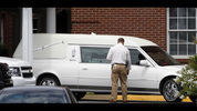 A Tuscaloosa police officer stands by the hearse as it leaves the University Church of Christ after a service for Cooper Harris on Saturday, June 28, 2014, in Tuscaloosa, Ala. Harris, 22 months old, died in Georgia on June 18 after he was left in his fathers' SUV for seven hours. (AP Photo/Butch Dill)