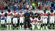 Grady Jarrett and Dontari Poe take a knee during the playing of the national anthem prior to the start of the game against the Detroit Lions at Ford Field on September 24, 2017 in Detroit, Michigan.