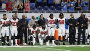 Atlanta Falcons defensive tackles Grady Jarrett (97) and Dontari Poe (92) take a knee during the national anthem before an NFL football game, Sunday, Sept. 24, 2017, in Detroit.