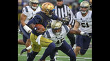 Brandon Wimbush #7 of the Notre Dame Fighting Irish holds off D.J. Palmore #45 of the Navy Midshipmen at Notre Dame Stadium on November 18, 2017 in South Bend, Indiana.