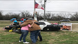 Strangers hug at the memorial for fallen officer Chase Maddox