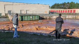 Carson Akney (left) and Father, Harry Akney (Right) take pictures of the rushing water behind Atlanta Wholesale Company on Buford Highway.
