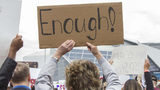 "A woman holds up a sign reading ""Enough!"" during the March for our Lives event in Atlanta, Georgia, on Saturday, March 24, 2018. (REANN HUBER/REANN.HUBER@AJC.COM)"