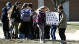 Students hold a sign during a student walkout outside Perry Hall High School in Perry Hall, Md., Wednesday, March 14, 2018.