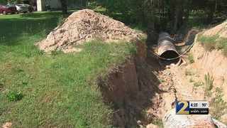 Woman says she paid thousands to remove drainage pipe from front yard