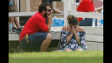 A woman prays in the grass outside the Alamo Gym where parents wait to reunite with their kids following a shooting at Santa Fe High School Friday, May 18, 2018, in Santa Fe, Texas. (Michael Ciaglo/Houston Chronicle via AP)