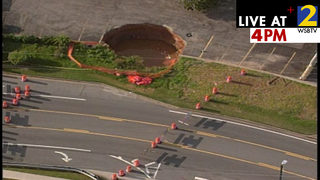 2 sinkholes swallow pine tree, close street near shopping center