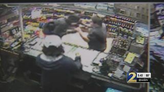 Surveillance video shows clerk fight back robber at liquor store