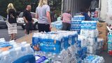 Volunteers prepare packages of bottled water to be delivered from Atlanta to Houston after Hurricane Harvey.