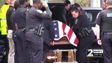 Officers salute casket carrying fallen colleague