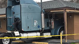 Semi plows into motel, barely missing woman inside