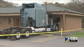 Big rig plows into motel, barely misses woman inside