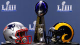 JANUARY 30: Detail of the Lombardi Trophy and the helmets of the New England Patriots (left) and the Los Angeles Rams prior to NFL Commissioner Roger Goodell speaking during a press conference. (Photo by Mike Zarrilli/Getty Images)