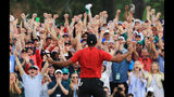 Patrons cheer as Tiger Woods celebrates after sinking his putt on the 18th green to win during the final round of the Masters at Augusta National Golf Club on April 14, 2019 in Augusta, Georgia. (Photo by David Cannon/Getty Images)