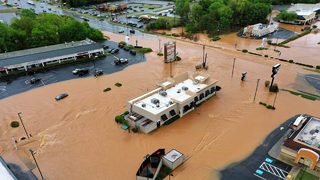 Fast-rising floodwaters trap nearly a dozen people inside cars, stores