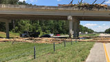 Tractor trailer carrying logs overturns on bridge over I-575.