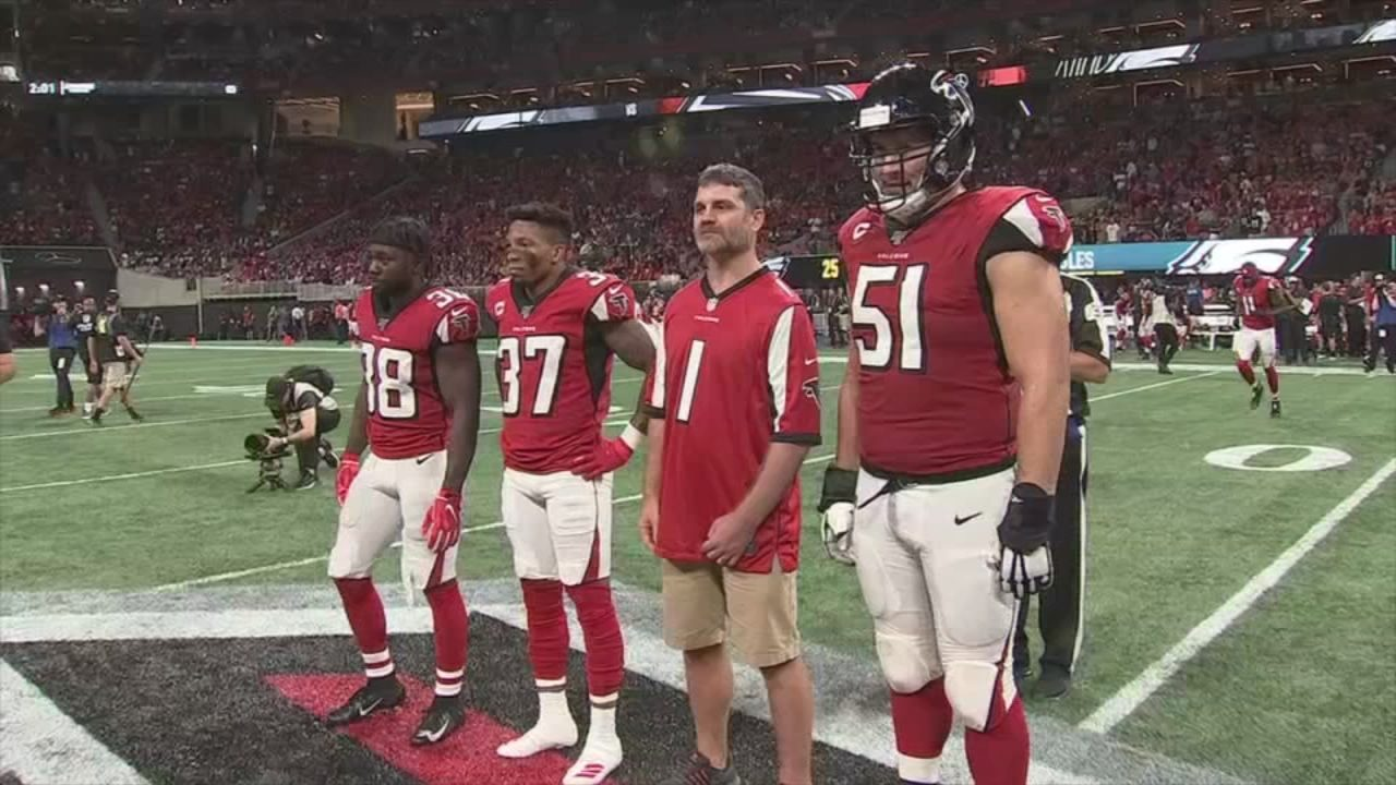 Officer Matt Cooper serves as Falcons honorary captain against Eagles