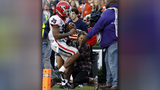 Georgia running back Brian Herrien (35) runs out of bounds and into a photographer during the first half of an NCAA college football game against Auburn, Saturday, Nov. 16, 2019, in Auburn, Ala. (AP Photo/Butch Dill)